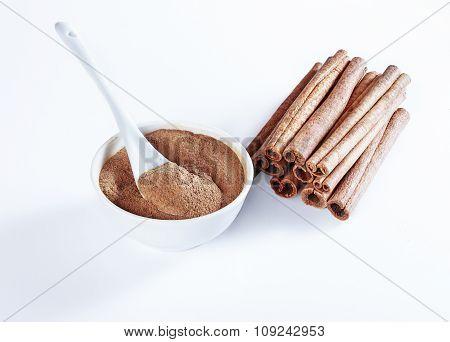 Ground Cinnamon In A Ceramic Bowl, Ceramic Spoon, Cinnamon Whole.