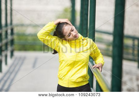 Young Asian Woman Exercising Outdoor In Yellow Neon Jacket, Stretching