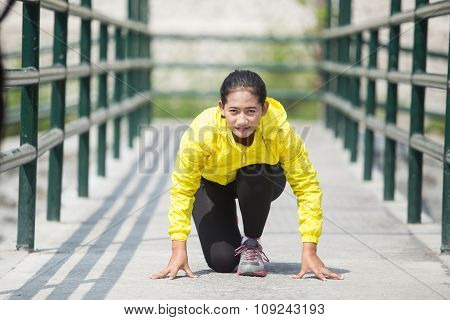 Young Asian Woman Exercising Outdoor In Yellow Neon Jacket, Getting Ready For Sprinting