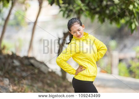 Young Asian Woman Exercising Outdoor In Yellow Neon Jacket, Injured Her Waist