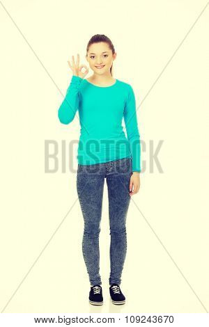 Casual young woman showing perfect sign.