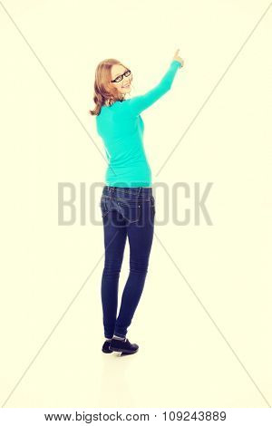 Happy teenage woman pointing up