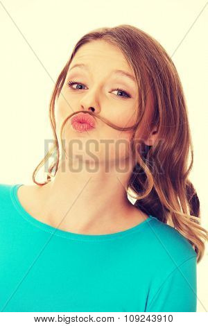 Happy teenage woman making moustache from hair