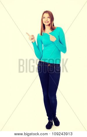 Happy teenage woman pointing with both hands