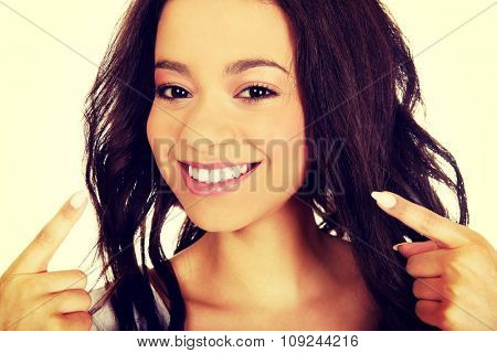 Beautiful african woman pointing to teeth.