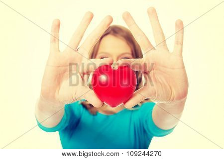 Teenage woman holding heart model