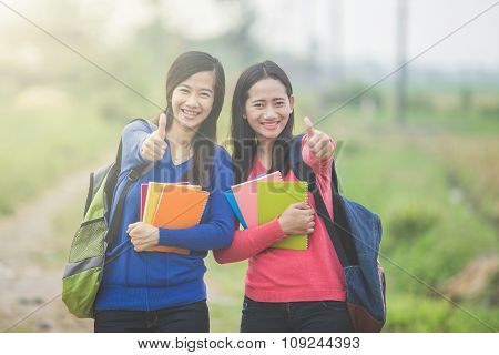 Two Young Asian Students Holding Books And With A Thumb Up Gesture