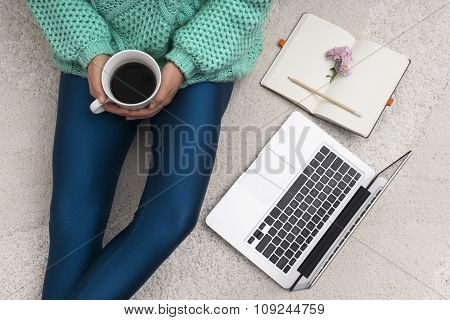 Laptop, Notebook And A Cup Of Coffee In Girl's Hands Sitting On A White Carpet