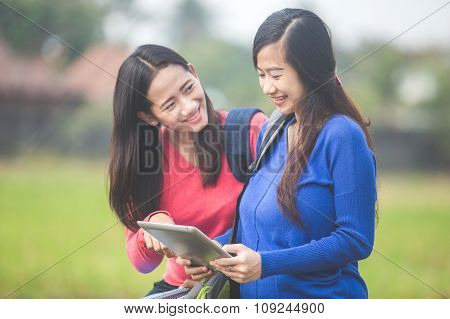 Two Young Asian Students Using Tablet Pc