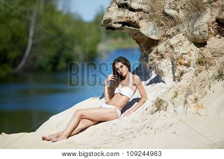 young woman in a swimsuit posing outdoor in a bright sun