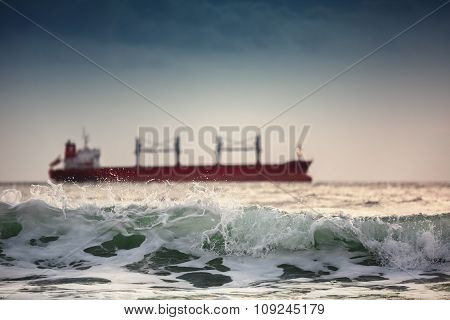 Sun Setting At The Sea With Sailing Cargo Ship
