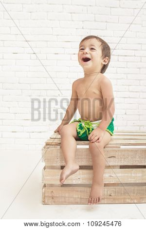 Cute Handsome Toddler Laughing While Sitting On Wooden Box