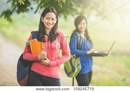 Asian Students With Her Friend Standing At The Background Holding Laptop
