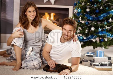 Happy attractive young couple caressing sleeping dachshund puppy at christmas morning.