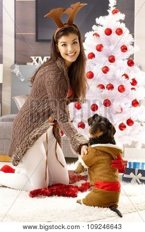 Happy woman kneeling by christmas tree, wearing reindeer antler, smiling, playing with dog.