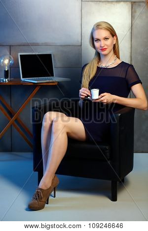 Attractive young blonde businesswoman having coffee-break, smiling, looking at camera.