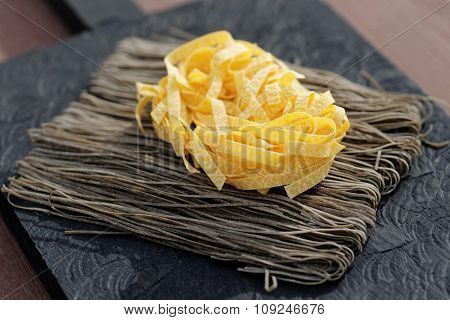 Two types of pasta on wooden plank, sunlight photo