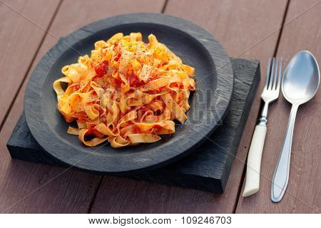 Tagliatelle with tomato sauce in wooden plate, outdoor shot