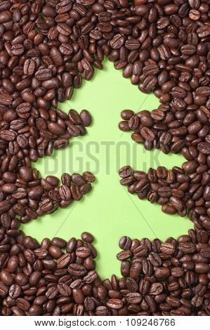 Coffee Beans Scattered On Green Paper With Drawn Christmas Tree