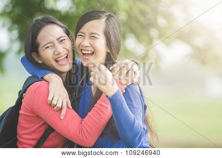 Two Young Asian Students Laugh, Joking Around Together