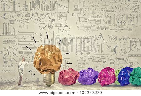 Businesswoman and many crumpled balls of colorful paper as creativity sign
