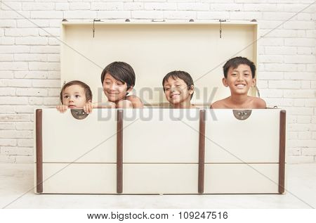 Four Brothers Playing Inside Crate