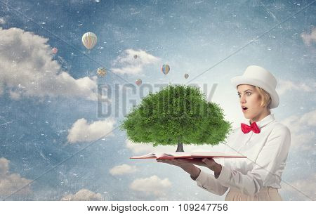 Young woman in white hat with opened book in hands and green tree on pages