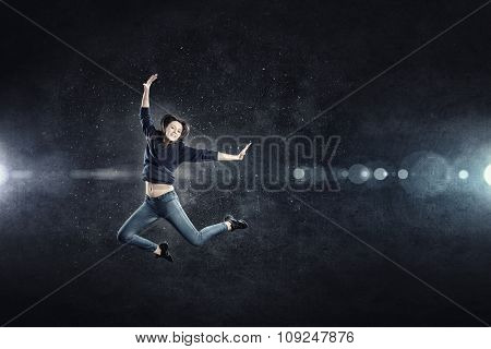 Young woman dancer jumping in spotlights on dark background