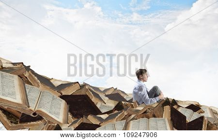 Young businessman sitting on pile of old books