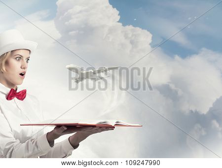 Young woman in white hat with opened book in hands and airplane flying out