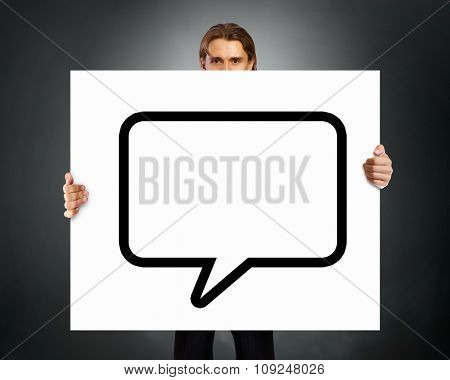Young businessman showing blank white speech banner. Place for text