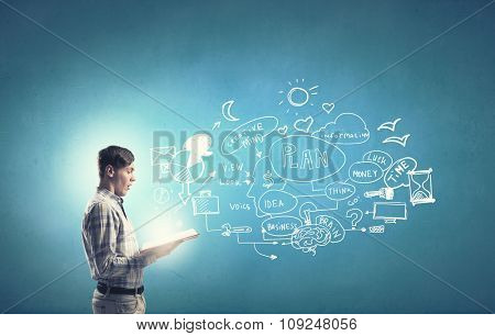 Young businessman with opened book in hands on blue background