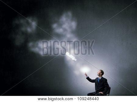Energy saving light bulbs and businessman in chair