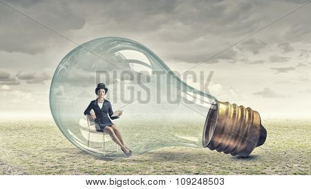 Young woman with tablet pc sitting inside of glass light bulb