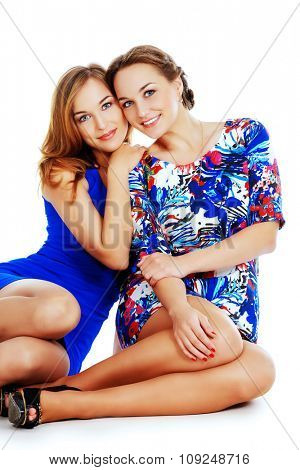 Two beautiful twin sisters hugging each other and smiling. Isolated over white.