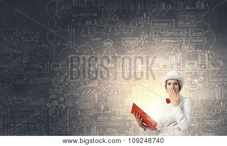 Young woman in white hat with opened red book in hands