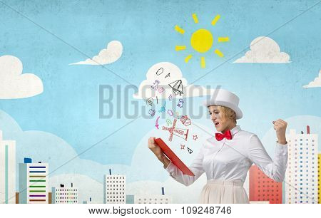 Young emotional woman in white cylinder with book in hand
