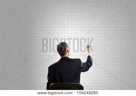 Rear view of businessman in chair writing on wall
