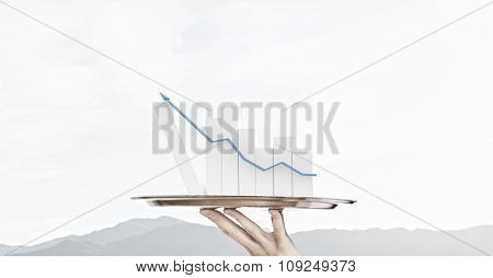 Human hand holding silver plate with growing chart