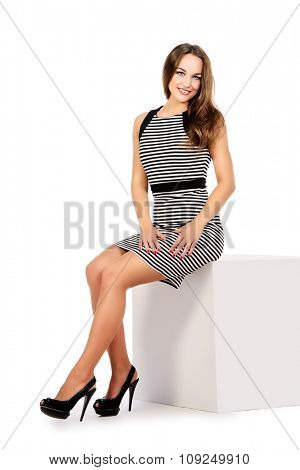 Pretty young woman in dress smiling at camera. Studio shot. Full length portrait.