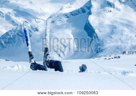Adult skier lying in deep snow at the ski resort