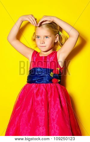 Pretty little girl posing in bright pink dress over yellow background. Fashion shot. Childhood.