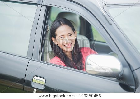 Young Asian Woman Driving A Car, Smiling To The Camera