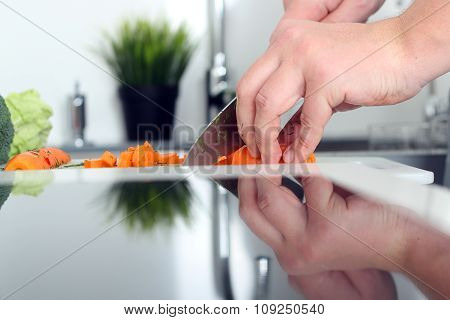 Food, Family, Cooking And People Concept - Man Chopping A Carrot On Cutting Board With Knife In Kitc