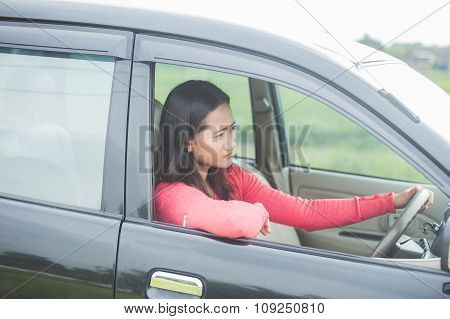 Young Asian Woman Driving A Car With Serious Face