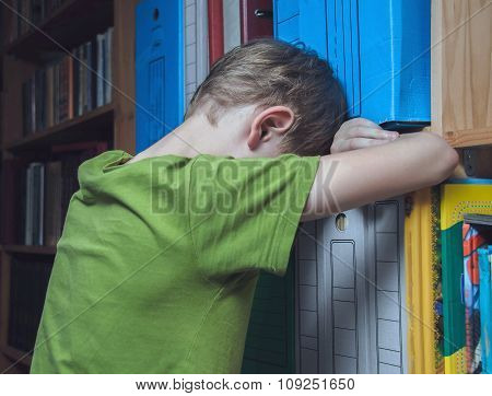 sad boy leaning against a bookcase