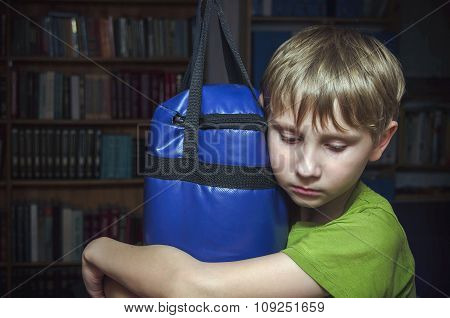 sad little boy hugs a punching bag