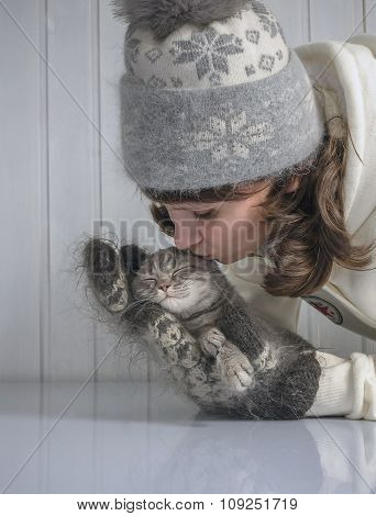 girl kisses a little kitten warming it in a warm gloves