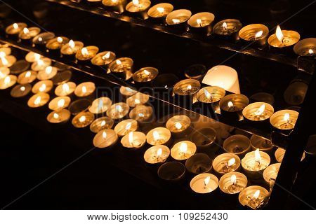 Large Group Of Small Candles Burning On Shelves
