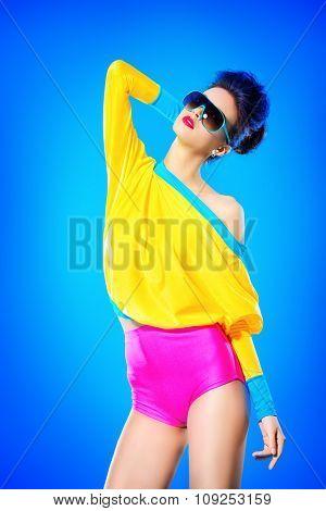Glamorous fashion model posing in vivid colourful clothes and sunglasses. Bright fashion. Optics, eyewear. Studio shot.